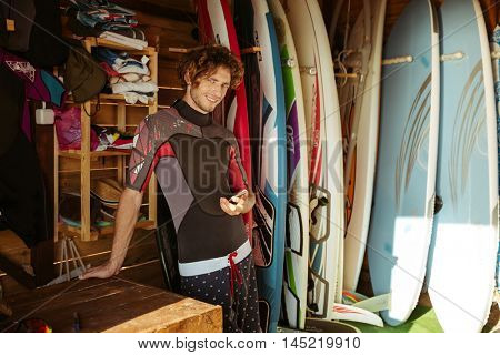 Smiling young man in swimsuit using smartphone while standing in the surf shack