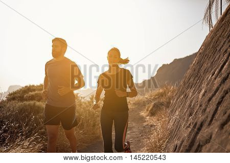 Young Couple Jogging Down A Mountain