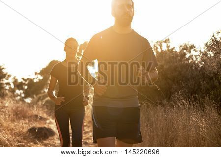 Competitive Couple Jogging Out In Nature