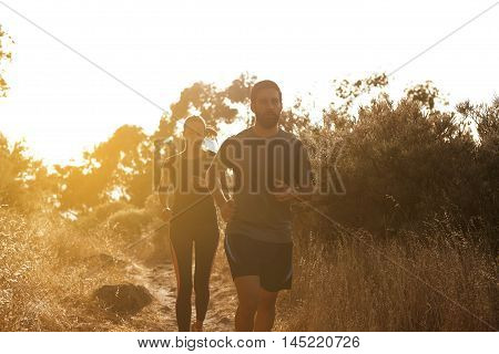 Young Couple Running In Bright Sunshine