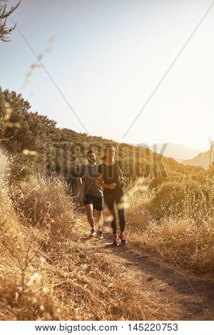 Young Couple Running On A Dusty Path
