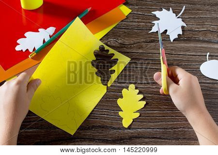Autumn Colored Paper Leaves On The Wooden Background. The Child Cuts Out Paper Leaves. Sheets Of Pap