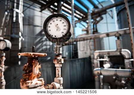 Closeup of manometer measuring gas pressure. Pipes and valves at industrial plant.