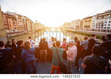 Florence, Italy - May 25, 2016: Tourists enjoy beautiful sunset on Ponte Vecchio bridge in Florence. Florence is the most popular city among the tourists in Tuscany