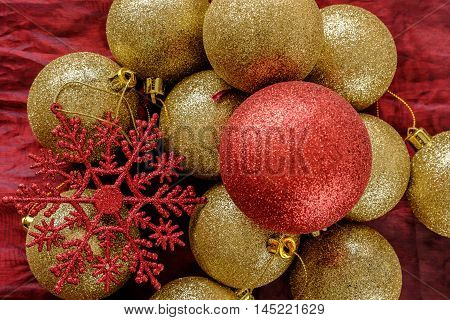 Selection of bright gold and red glitter Christmas tree decoration baubles with red snowflake on red cloth background