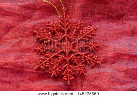 Bright red glitter snowflake Christmas tree decoration with gold cord on red cloth background