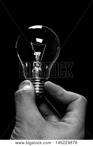 incandescent bulb held between the fingers of a hand in the dark key