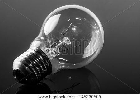 incandescent bulb resting on a shiny black background