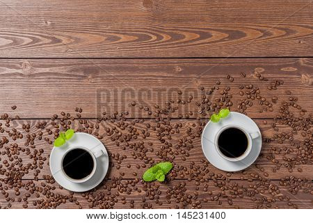 White porcelain coffee cup with coffee beans on wooden table