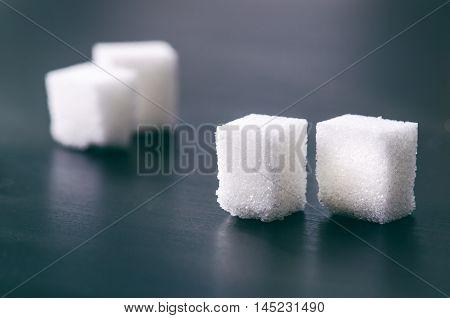 Cubes of sugar on a dark background. Unhealthy ingredients. Lump sugar