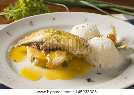 Fried Tilapia Served With Rice On White Plate.