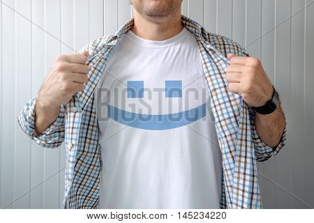 Man stretching shirt to reveal smiley emoticon printed on chest