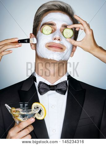 Gentleman receiving spa facial treatment. Photo of Handsome man with a facial mask on his face and cucumber on his eyes. Grooming himself