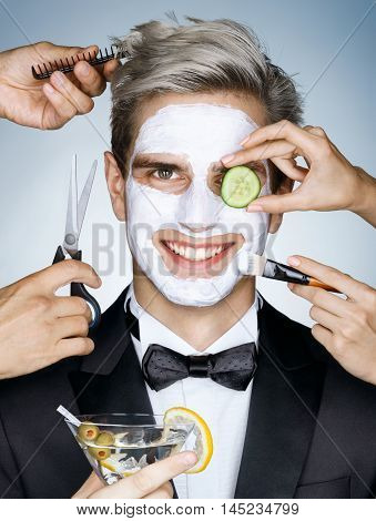 Happy elegant man with moisturizing facial mask surrounded by the multifunctional service (stylist beautician hairdresser). Photo of happy stylish man receives the spa treatments. Grooming himself