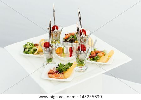 Catering food. On a beautiful white square plate lined with snacks.