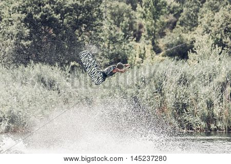 Wakeboarder jump over the lake. Tonned photo, faded colors.