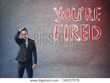 Front view of a businessman with his hand on his head looking contritely with 'you're fired' words beside him. Losing a job. Stress and depression. Unemployed.