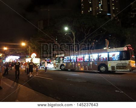 HONOLULU - DECEMBER 5: People explore Christmas light display on King street with buses and other vehicles celebrating the holidays. Honolulu Hawaii on December 5 2015.