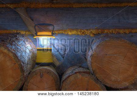 Luminous hand lantern and axe standing on the lumber