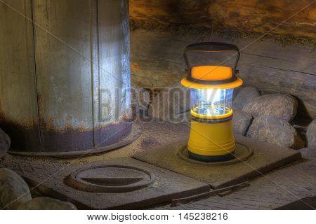Luminous hand lantern standing on the stove near the chimney