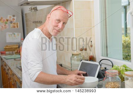 a senior man cooking in the kitchen with tablet at home