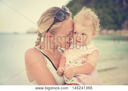 smiling mother hugs her little curly daughter while on vacation at the beach. Mom leaned to face the child. The concept of family happiness