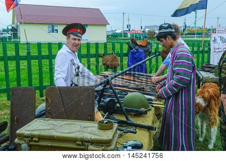 Tyumen, Russia - June 24, 2016: The 5th open championship of Russia on a plowed land. Senior cossack demonstrates rifles collection