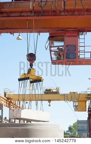 Tyumen, Russia - August 13, 2013: Finished goods warehouse at Concrete Goods Plant No. 5. The crane operator works outdoors