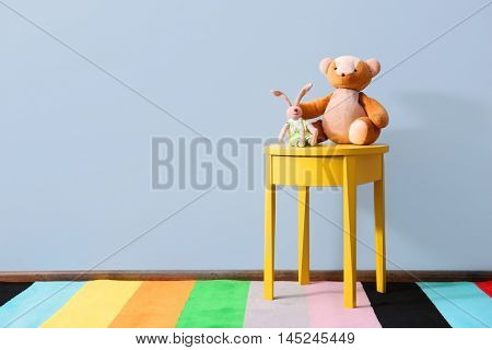Yellow bedside table with toys on blue wall background