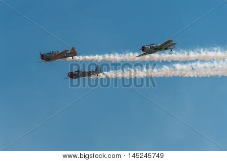 EDEN PRAIRIE MN - JULY 16 2016: Trio of AT-6 Texan airplanes trailing smoke fly across the blue sky at air show. The AT-6 Texan was primarily used as trainer aircraft during and after World War II.