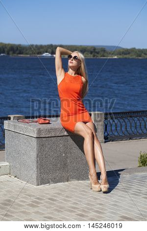 Portrait in full growth, young beautiful blonde woman in orange dress on the street, summer city outdoors