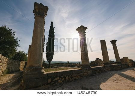 Some pillars of the roman ruins of Volubilis on a beautiful day with sunshine, blue sky and only few clouds photgraphed in horizontal format.