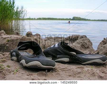 Flip-flops left bather on the sandy shore of a small lake