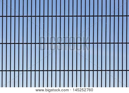 Wire mesh security fence with blue sky