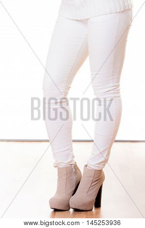 Winter fashion. Female legsin white pants foots in stylish fashionable shoes boots. Studio shot isolated