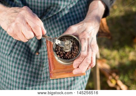 Old Woman Grinding Coffee On A Vintage Coffee Grinder