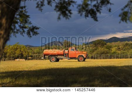 An old truck in a field before a storm
