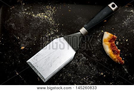 Leftover pizza crust on a black baking pan with a spatula