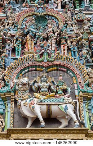 Madurai India - October 19 2013: Closeup of double scene the wedding of Shiva and Meenakshi and both sitting on Nandi the bull. Facade of West Gopuram at Meenakshi Temple.