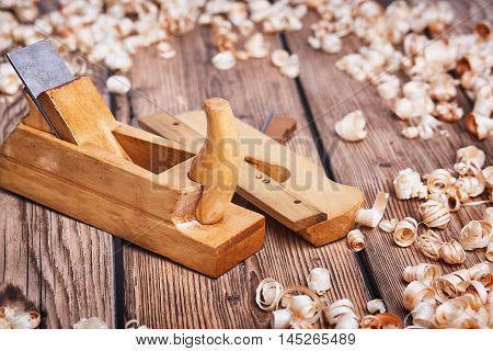 Wooden planer, table from old wood, natural building materials, woodwork and antique hand tools, carrying out carpentry, tool kit for joinery, wood sawdust, old wood texture