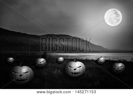 Background for Halloween holiday. Mountain and beautiful full moon at night. Pumpkins with scary face on the riverbank. Outdoors. The moon were NOT furnished by NASA. Black and white tone.