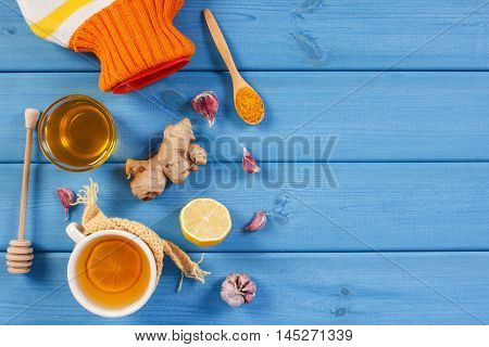Hot Water Bottle, Cup Of Tea And Ingredients For Preparation Warming Beverage