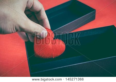 Human hand holding or putting a red heart-shaped in a black gift box for a Valentine's day concept of care and love. Vintage tone effect and low key picture style.
