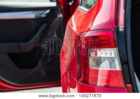 Close up of a back car light. Red car with open side door and trunk.