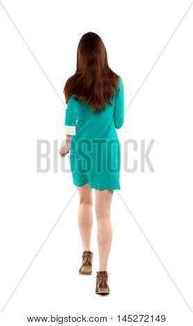 back view of running woman. beautiful girl in motion. Long-haired brunette in a green dress runs away into the distance.