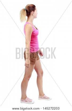 back view of walking woman . going gir in motion. Isolated over white background. Sport blond in brown shorts and misses looking to the side.
