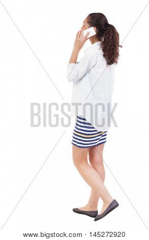 a side view of a woman walking with a mobile phone. beautiful curly girl in motion.  backside view of person.  Rear view people collection. Isolated over white background.  African-African-American