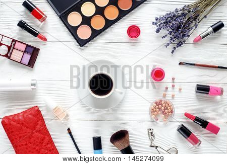make up set on wooden table with lavender, coffe cup and glasses top view