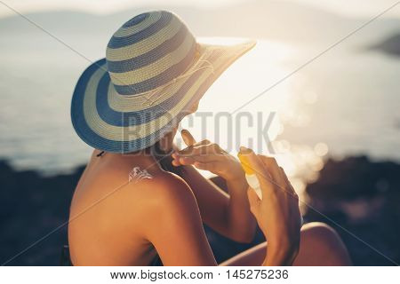 Young woman holding bottle of sunscreen lotion spraying sunblock cream on shoulder before tanning