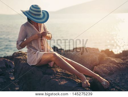 Woman sitting on the cape by the sea